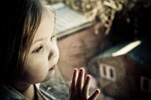 Kleines Mädchen schaut traurig aus dem Fenster