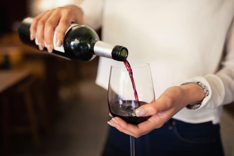 Frau schüttet Wein in Glas
