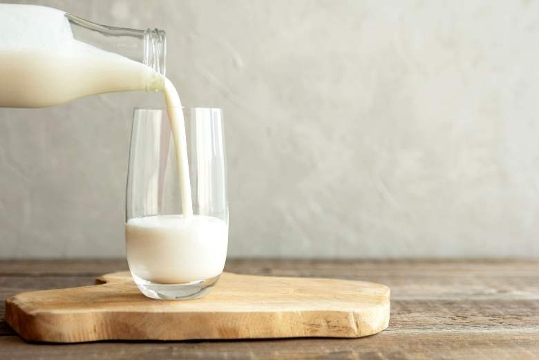 Ein Glas Milch eingießen